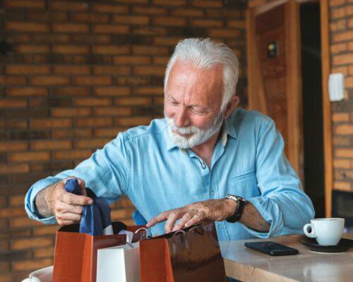 Senior man peeking into shopping bags at cafe