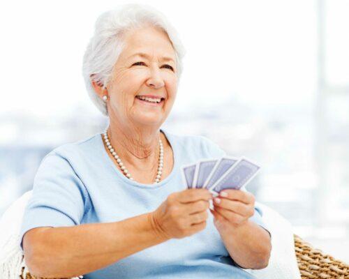 Happy senior woman playing cards while looking away at home. Horizontal shot.